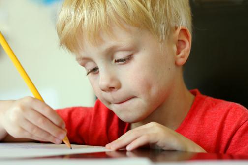 boy writing in school notebook