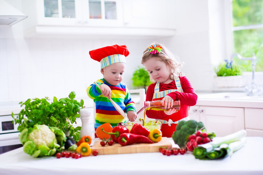 two kids cooking vegetables