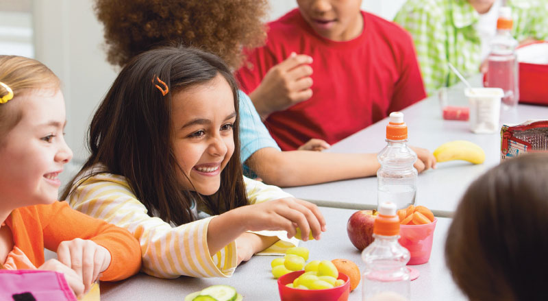 young girl smiles at lunch table with healthy food