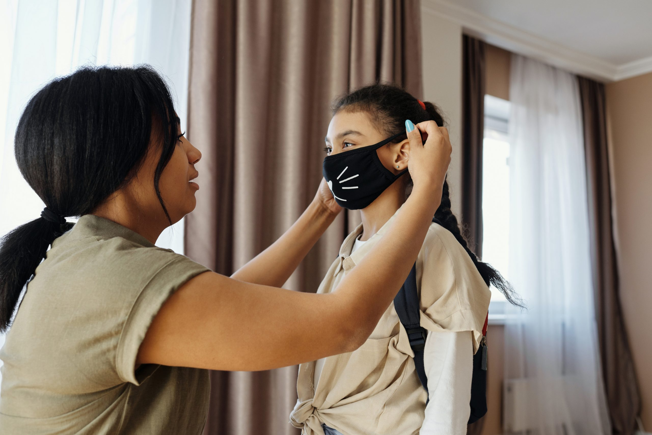 girl putting on mask