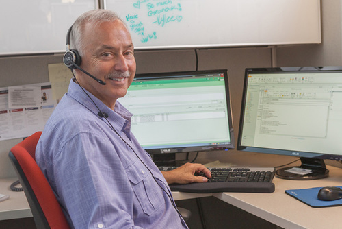 photo of a man with headset sitting in front of a computer