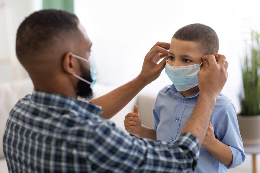 Dad putting mask on child